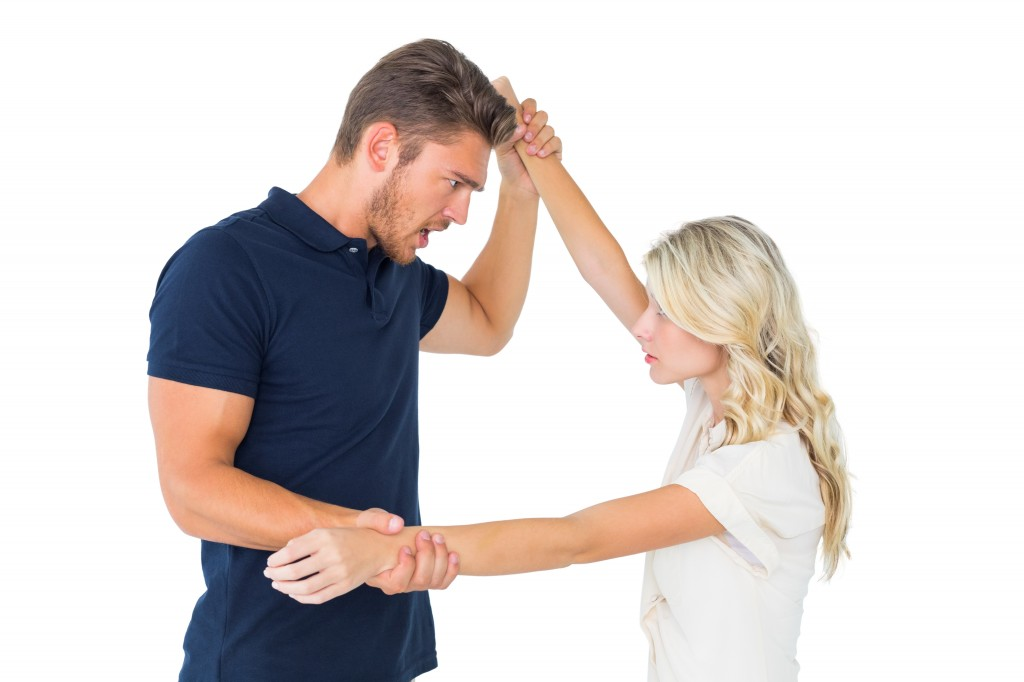 Angry man overpowering his girlfriend